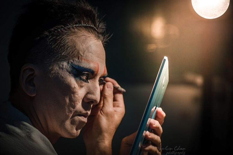 Chinese opera performer putting on make up