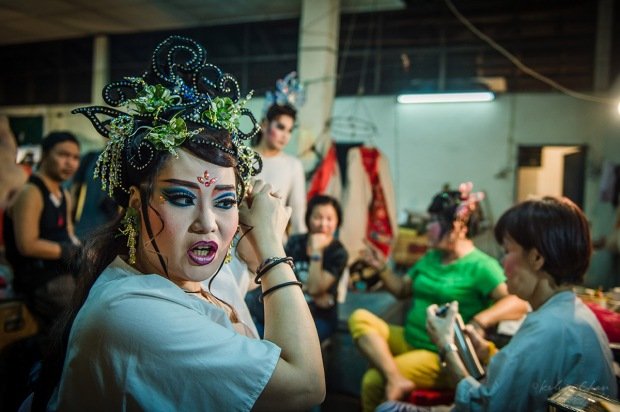 Chinese opera performer putting on make up at back stage